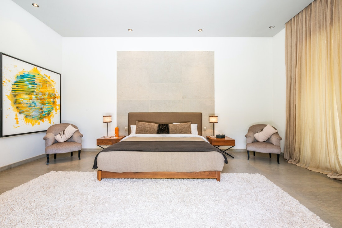 Minimalist bedroom with wooden bed at Marhba luxury private villa in Marrakech