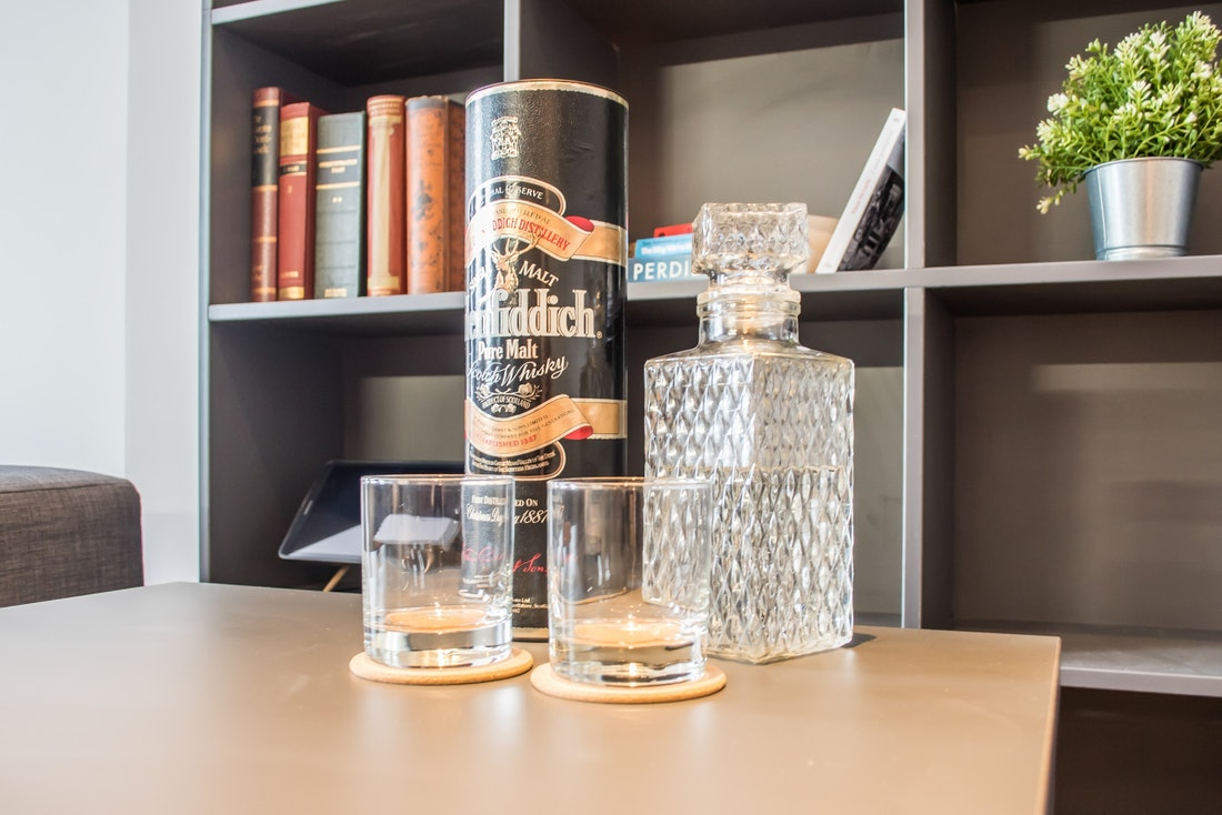 A bottle of Glenfiddich whiskey with two empty whisky glasses