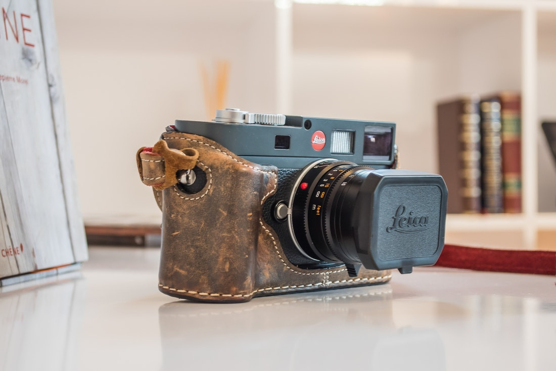 Vintage Leica film camera with a brown leather case