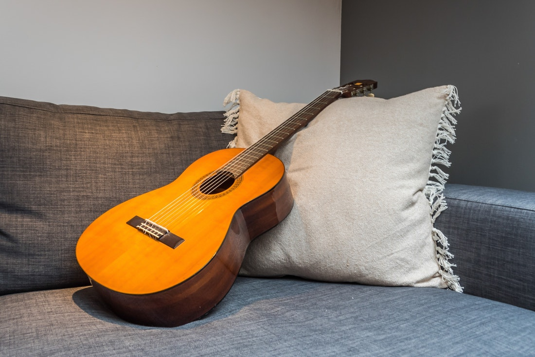 Brown guitar grey couch family apartment Takian Morzine