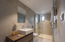 Grey modern bathroom with shower at Sugi accommodation in Morzine
