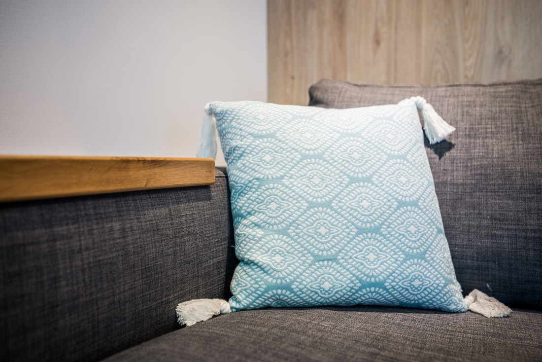 Blue and white pillow on a grey couch