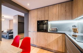 Wooden kitchen with red chairs at Karri accommodation in Morzine