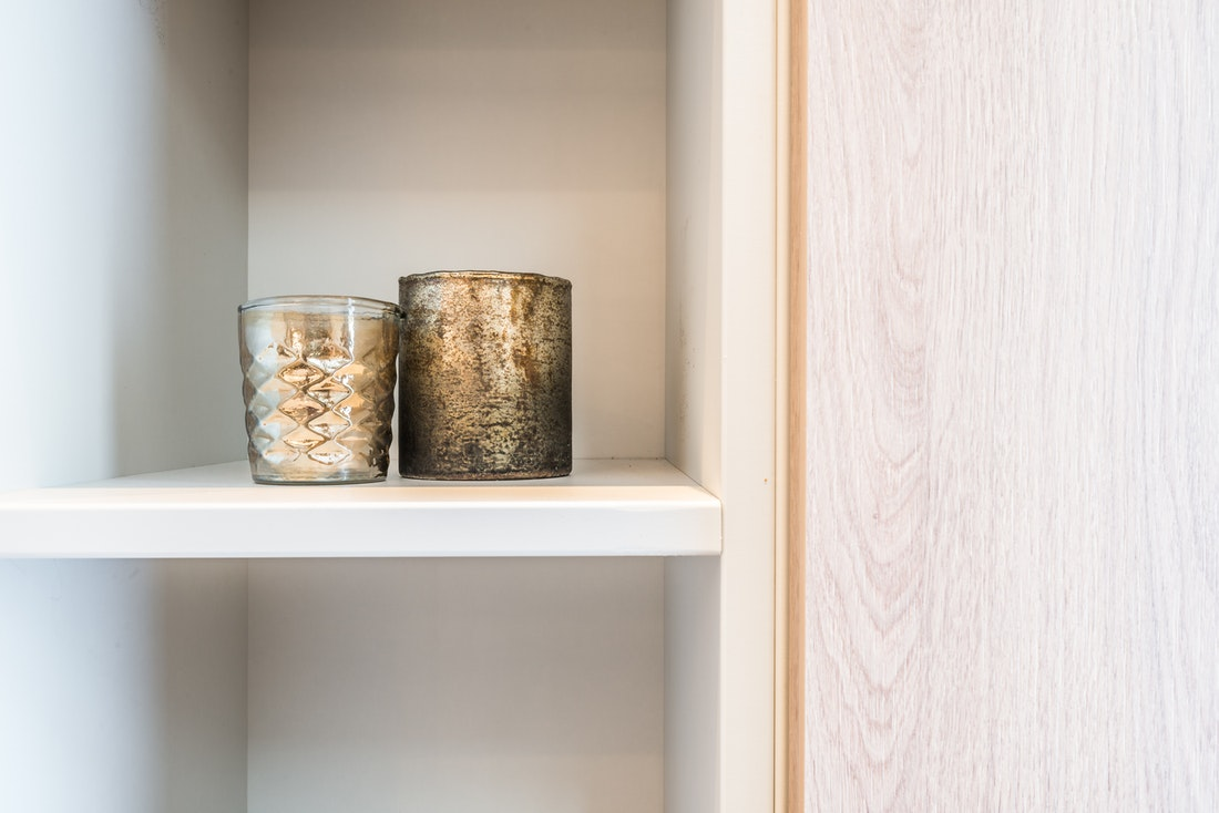Two metallic candles on a white shelf at Kauri accommodation in Morzine